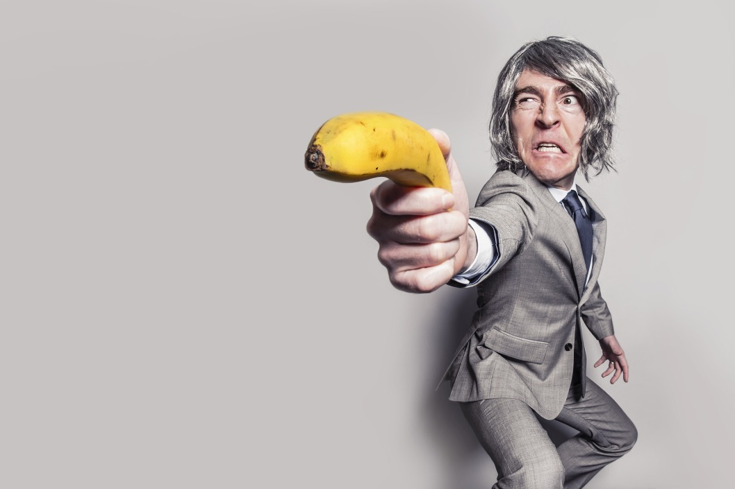Man using banana as a gun